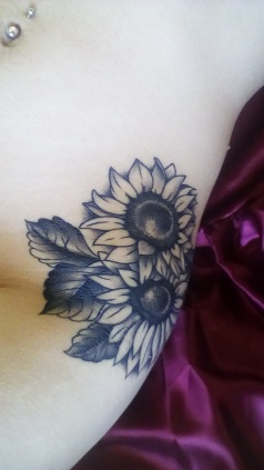 Flower tattoo on right side of body above hips